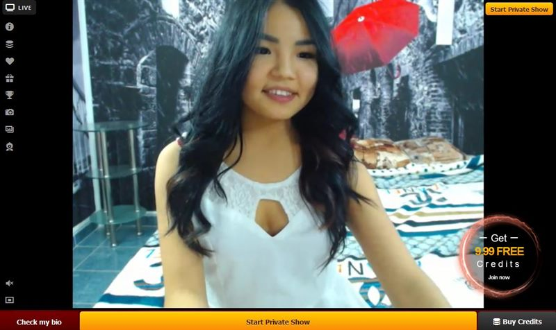 An Asian webcaht host in white smiles for the camera on LiveJasmin.com